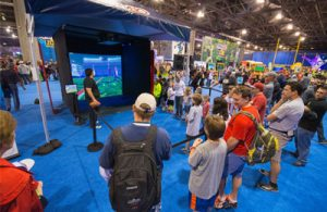 Crowd Gathered around indoor golf simulator